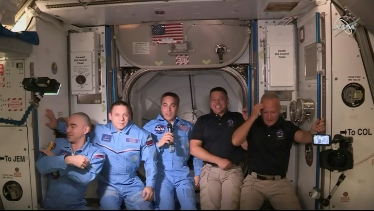 Douglas Hurley (R) and Robert Behnken (2ndR) arrive at the International Space Station, to be greeted by other astronauts | AFP