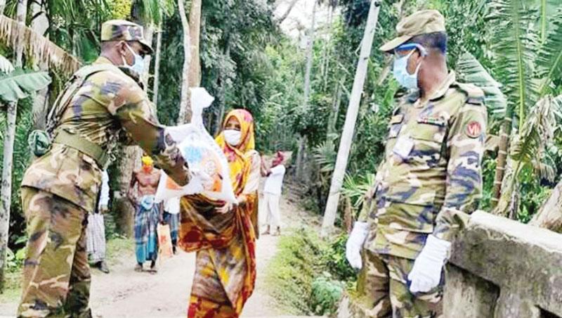 Members of Bangladesh Army handing over agri seeds to a farmer