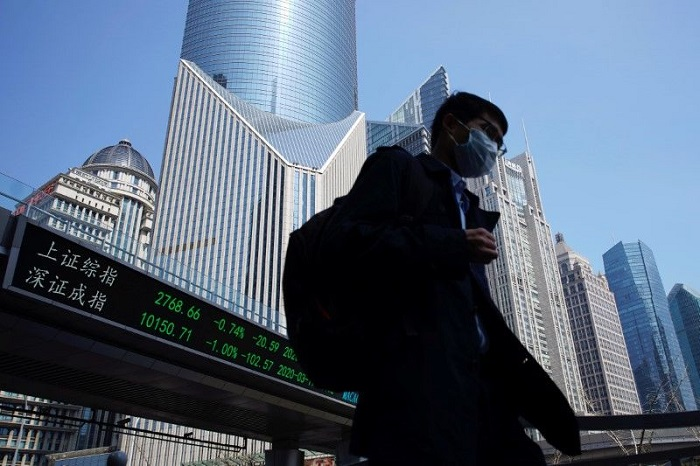 FILE PHOTO: A pedestrian wearing a face mask walks near an overpass with an electronic board showing stock information, following an outbreak of the coronavirus disease (COVID-19), at Lujiazui financial district in Shanghai, China March 17, 2020. REUTERS/Aly Song
