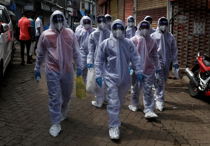 Healthcare workers wearing personal protective equipment (PPE) walk towards different localities before the start of a check-up camp for the coronavirus disease (COVID-19) in Mumbai, India June 27, 2020. REUTERS/Francis Mascarenhas