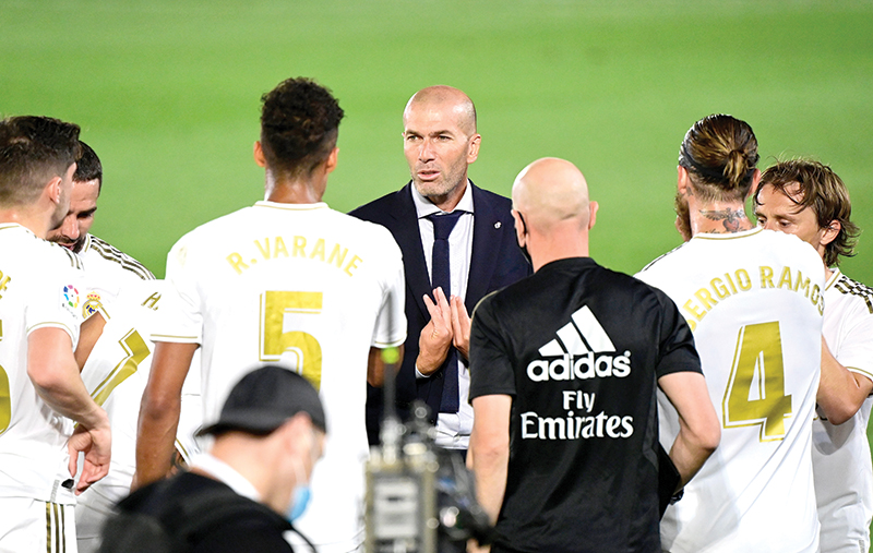 Real Madrid's French coach Zinedine Zidane talks to his players during the Spanish League football match Real Madrid CF against RCD Mallorca at at the Alfredo di Stefano stadium in Valdebebas, on the outskirts of Madrid, on June 24, 2020.