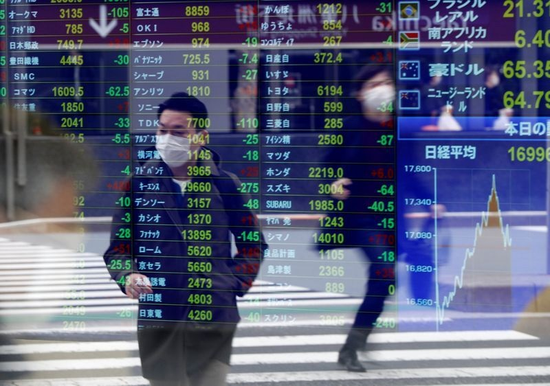 FILE PHOTO: Passersby wearing protective face masks following an outbreak of the coronavirus disease (COVID-19) are reflected on a screen displaying stock prices outside a brokerage in Tokyo, Japan, March 17, 2020. REUTERS/Issei Kato