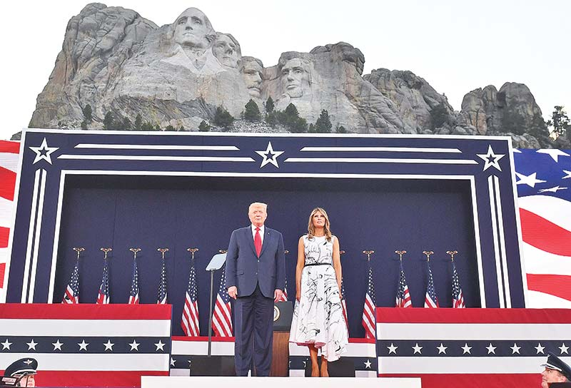 US President Donald Trump and First Lady Melania Trump pay their respects as they listen to the National Anthem during the Independence Day events at Mount Rushmore National Memorial in Keystone, South Dakota on July 3.	photo : AFP