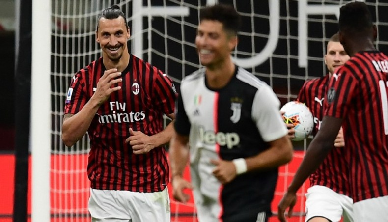 AC Milan forward Zlatan Ibrahimovic (L) reacts next to Juventus superstar Cristiano Ronaldo (C) after scoring from a penalty during their Serie A match at the San Siro stadium in Milan on Tuesday. Photo: AFP