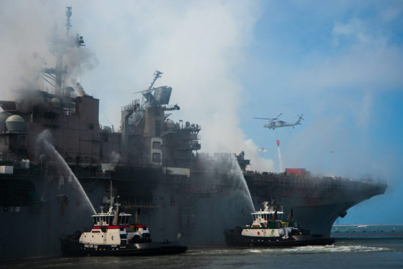 """SAN DIEGO (July 13, 2020) An MH-60S Seahawk helicopter from the """"Merlins"""" of Helicopter Sea Combat Squadron (HSC) 3, provides aerial firefighting support alongside Sailors and civilian fire crews on the ground to fight the fire aboard amphibious assault ship USS Bonhomme Richard (LHD 6). U.S. Navy Photo"""