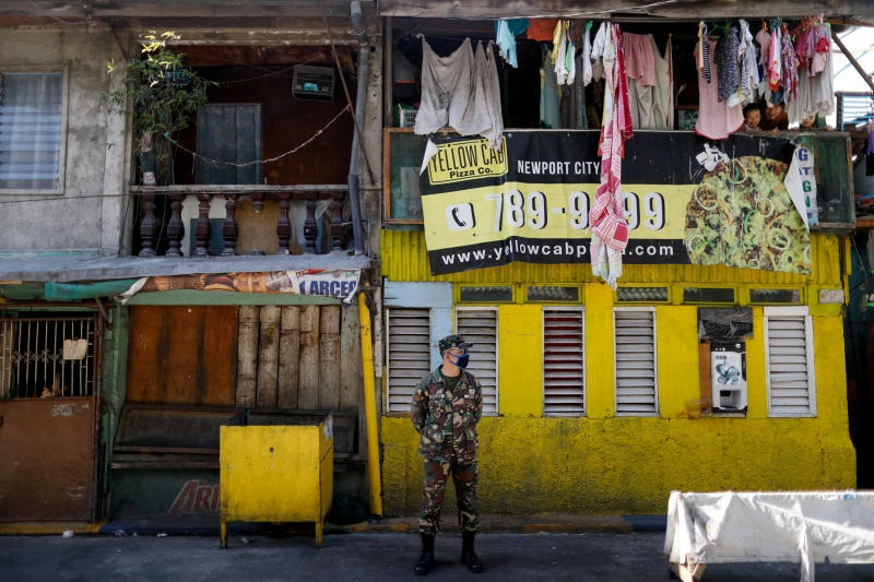 A soldier wearing a protective mask guards a street while children look out from a balcony, as the city undergoes a stricter lockdown to contain the coronavirus disease spread, in Pasay City, Philippines, April 22, 2020. File photo: Reuters