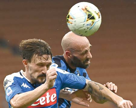Napoli's Portuguese defender Mario Rui (L) heads the ball with Inter Milan's Spanish midfielder Borja Valero during the Italian Serie A football match Inter Milan vs Napoli played behind closed doors at the San Siro Stadium in Milan on July 28, 2020.