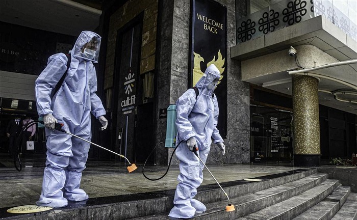 Employees disinfect a closed mall in Mumbai, India, July 30, 2020. India recorded the highest ever single-day spike of 55,078 of fresh COVID-19 cases on Friday, taking the total tally to 1,638,870, according to the federal health ministry's latest data. (Str/Xinhua)