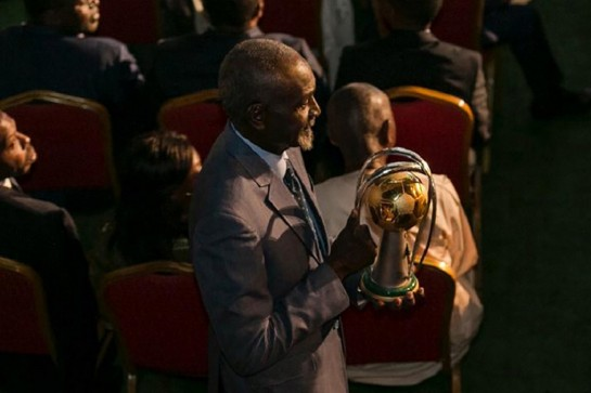 Former Cameroonian football captain Stephen Tataw carries the trophy of the African Championship of Nations (CHAN) to the stage during the drawing ceremony in Yaounde, on February 17, 2020. Photo: AFP