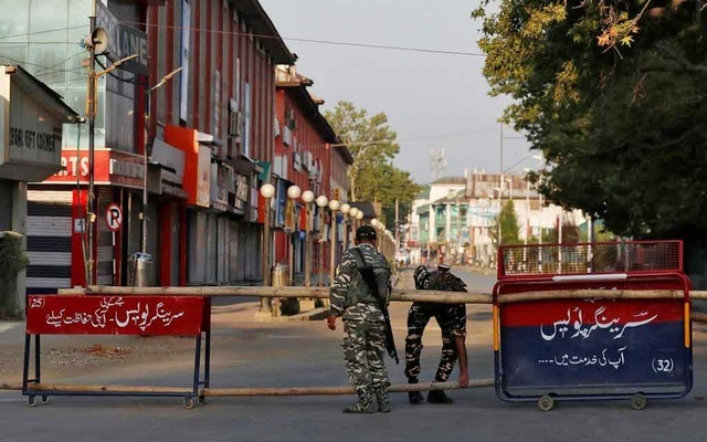 Indian Central Reserve Police Force (CRPF) officers put up a roadblock on an empty street during a lockdown on the first anniversary of the revocation of Kashmir's autonomy, in Srinagar August 5, 2020. REUTERS/Danish Ismail