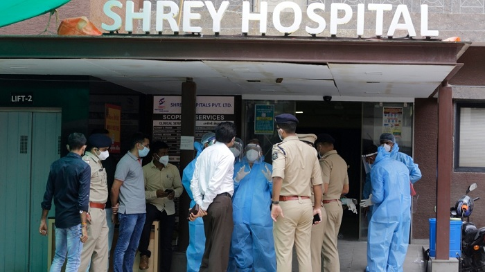 Forensic officers, wearing protective equipment, talk with police and government officers at Shrey hospital, where a fire broke out early morning in Ahmedabad, India, Thursday, Aug. 6, 2020. (AP Photo)