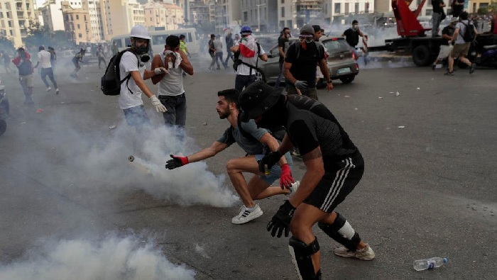 Demonstrators hurl stones during a protest near the parliament building following Tuesday's blast, in Beirut, Lebanon August 8, 2020.(REUTERS)