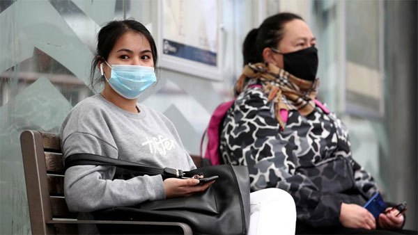 People in face masks wait for a bus in Auckland on the first day of New Zealand's new Covid-19 safety measure that mandates masks on public transport. August 31, 2020. (Reuters)