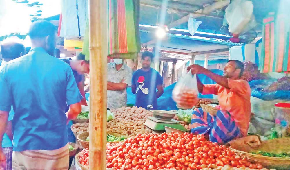 A wholesaler weighing onion at Kawran Bazar in the capital on Tuesday. Onion prices in the country jumped by more than 50 per cent on Tuesday.	PHOTO: OBSERVER