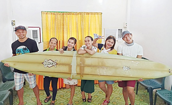 Filipino teacher Giovanne Branzuela (L) poses with the surfboard, once owned by big wave surfer Doug Falter who lost it while surfing in Hawaii two years. Photo: Reuters