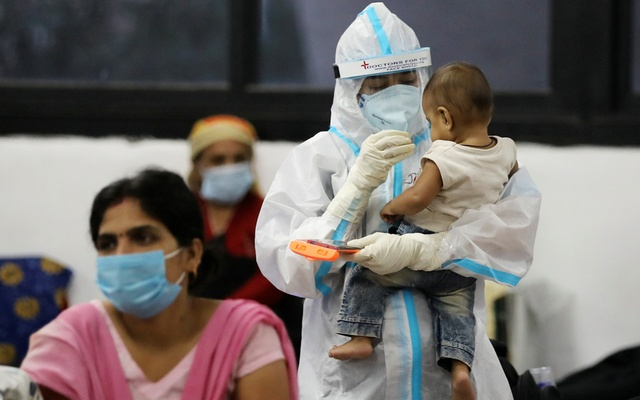 A medical worker in PPE plays with a child of woman recovering inside a quarantine centre for the COVID-19  patients amidst the spread of the disease at an indoor sports complex in New Delhi, India, September 22, 2020. Photo: Reuters