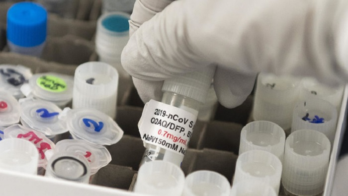 A doctor lifts a vial with a potential coronavirus, COVID-19, vaccine at Novavax labs in Gaithersburg, Maryland on March 20, 2020, one of the labs developing a vaccine for the coronavirus, COVID-19.(File/AFP)