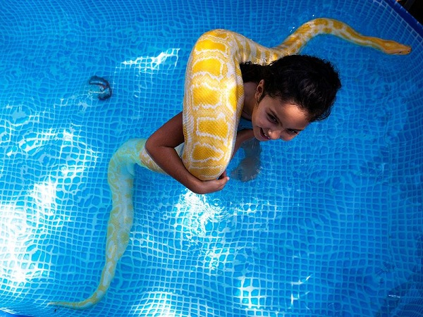 Eight-year-old Inbar likes to cool off in her small backyard pool in Israel with her favourite swimming buddy - her pet python.