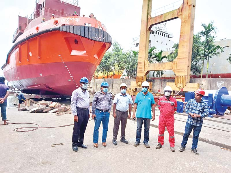 "Engineers of the Western Marine Shipyard (WMS) pose in front of tugboat ""Tiakhali-1"" before launching it on the Karnaphuli River in Chattogram on Saturday. The tugboat has been built for the Pangaon Port."