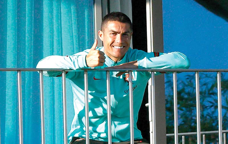 This handout picture released on October 13, 2020 by the Portuguese Football Federation shows Portugal�s forward Cristiano Ronaldo giving the thumb up as he watches his teammates training session from a balcony at Portugal�s training camp in Oeiras, on the outskirts of Lisbon on October 13, 2020. photo: AFP