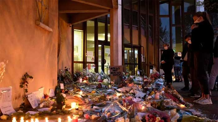 People stand in front of flowers and candles next to a placard reading 'I am a teacher, I am Samuel' at the entrance of a middle school in Conflans-Sainte-Honorine, 30kms northwest of Paris, on October 17, 2020, after a teacher was decapitated by an attacker who has been shot dead by policemen. © Bertrand Guay, AFP