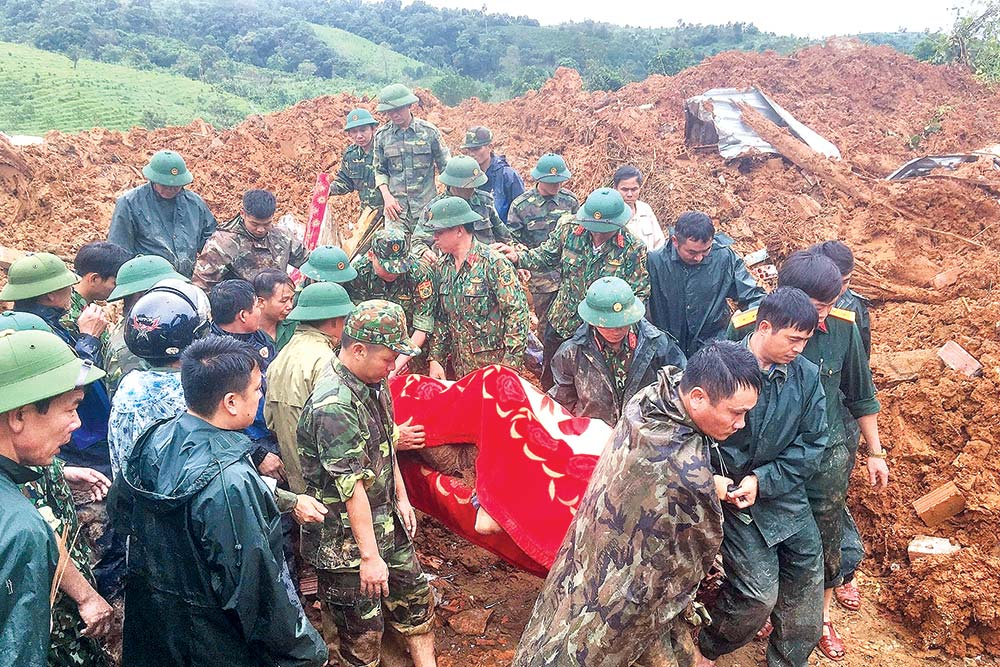Military personnel carrying a body recovered from the site of a landslide in central Vietnam's Quang Tri province on October 18.photo : AFP