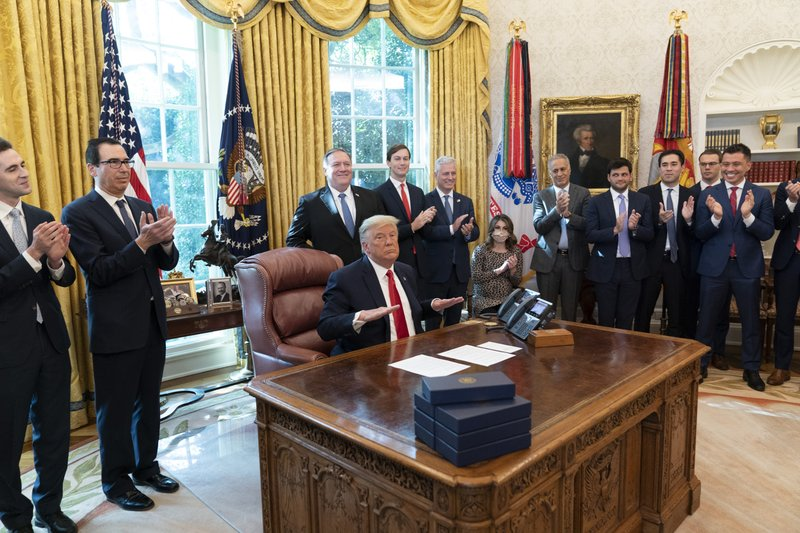 President Donald Trump reacts after hanging up a phone call with the leaders of Sudan and Israel, as Treasury Secretary Steven Mnuchin, second from left, Secretary of State Mike Pompeo, White House senior adviser Jared Kushner, National Security Adviser Robert O'Brien, and others applaud in the Oval Office of the White House, Friday, October 23, 2020, in Washington. Photo: AP/Alex Brandon