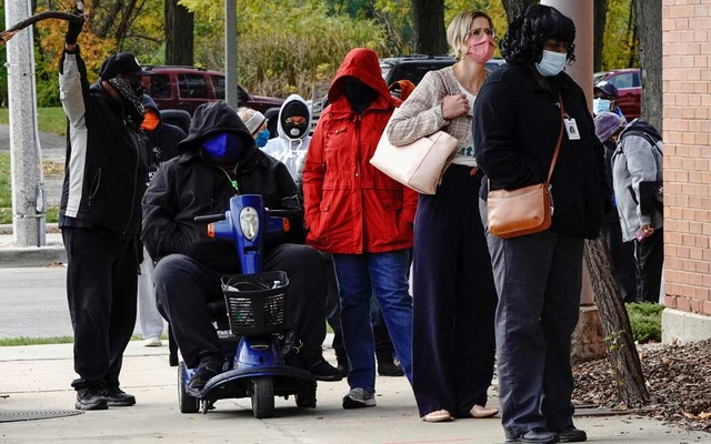 People wearing protective masks queue to enter a polling site at the Milwaukee Public Library's Washington Park location in Milwaukee, on the first day of in-person voting in Wisconsin, US, October 20, 2020. REUTERS/Bing Guan