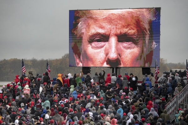 Supporters of President Donald Trump watch a video screen showing his face during a campaign event on Tuesday, Oct. 27, 2020, in Lansing, Mich. (Nicole Hester/Mlive.com - Ann Arbor News via AP)