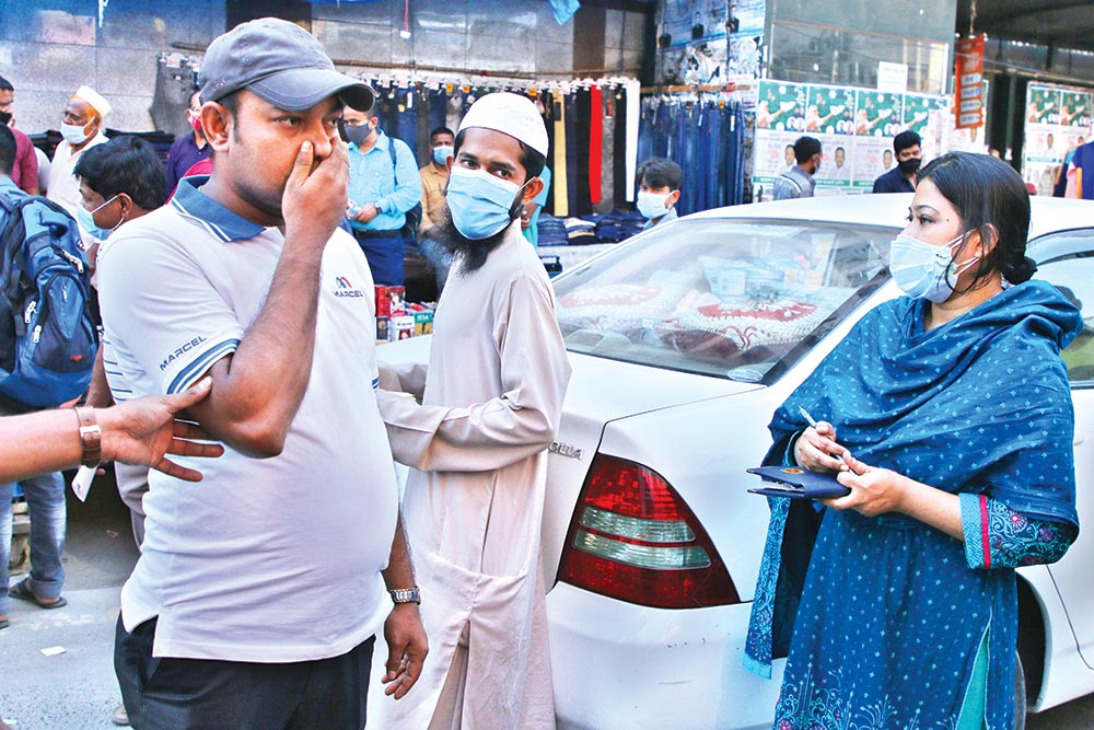 A man expresses his embrassment as a magistrate (R) appears before him while conducting a mobile court in an effort to curb the spread of the novel coronavirus on Tuesday (November 17, 2020). Mobile courts also fined some people for violating the health guidelines . This photo was  taken from Motijheel in the capital.PHOTO: OBSERVER