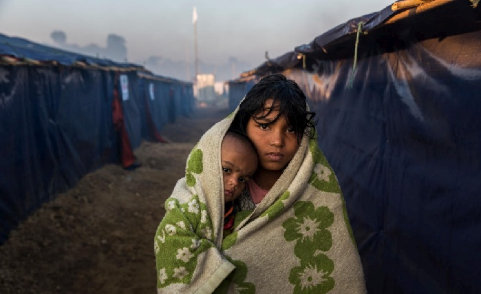 Rohingya refugee Morsheda, 12, and her 10-month-old niece, Nasima, go for a walk in the early morning at Kutupalong camp in southern Bangladesh to warm up from the cold inside their shelter.  © UNHCR/Andrew McConnell [FILE PHOTO]