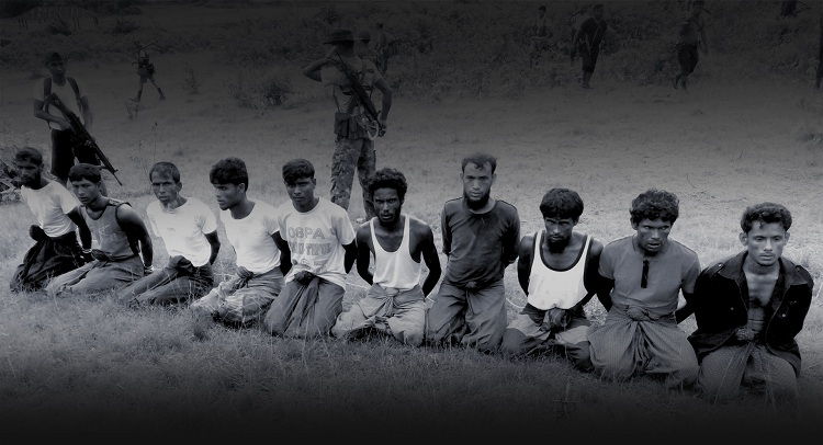 This photo was taken on the day the 10 Rohingya men were killed. Paramilitary police officer Aung Min, left, stands guard behind them. The picture was obtained from a Buddhist village elder, and authenticated by witnesses. Photo: Reuters