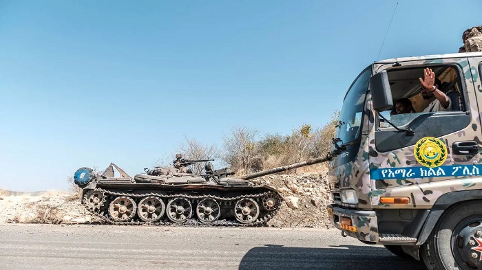A damaged tank stands abandoned on a road as a truck of the Amhara Special Forces passes by near Humera, Ethiopia on November 22, 2020. © Eduardo Soteras, AFP