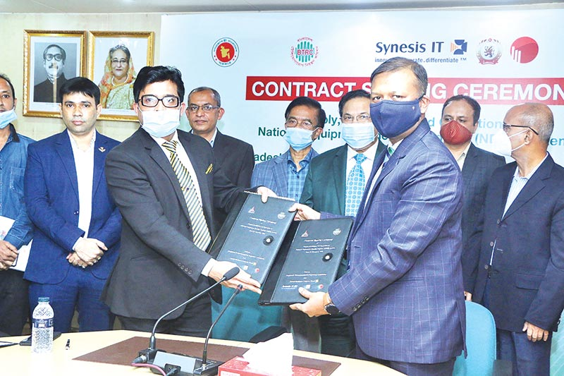 BTRC Director Lt. Col. Mohammod Faisol and Synesis IT Managing Director Shohorab Ahmed Chowdhury accompanied by their company colleagues exchange documents after signing an agreement on behalf of their respective organizations, at BTRC office in Dhaka on Wednesday.