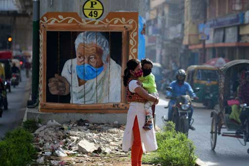 A woman and a boy wearing face masks are seen in front of a mural in Agartala, the capital city of India's northeastern state Tripura, on Nov. 25, 2020. Global COVID-19 cases surpassed 60 million on Wednesday, according to the Center for Systems Science and Engineering (CSSE) at Johns Hopkins University. (Str/Xinhua)