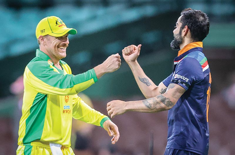 Australia's captain Aaron Finch (L) bumps fists with India's captain Virat Kohli after victory during the one-day international cricket match at the Sydney Cricket Ground (SCG) in Sydney on Friday. photo: AFP