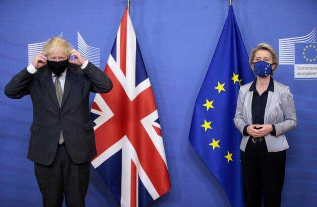 FILE PHOTO: British Prime Minister Boris Johnson adjusts his face mask as he meets European Commission President Ursula von der Leyen in Brussels, Belgium December 9, 2020. Olivier Hoslet/Pool via REUTERS/File Photo