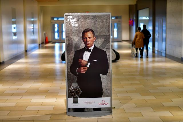 "Shoppers walk past an advertisement for the upcoming James Bond film ""NO TIME TO DIE"" whose release has been delayed due to the COVID-19 pandemic, at the Christiana Mall in Newark, Delaware US November 19, 2020. Photo: Reuters"