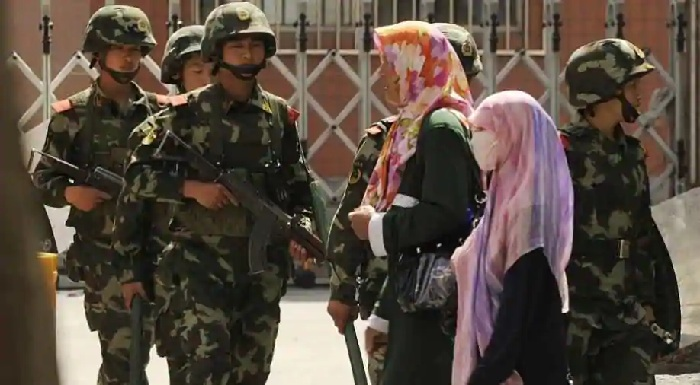 Chinese soldiers on the street keeping an eye on Uyghur women wearing veils Photograph: AFP