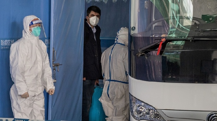 A member of the WHO team boards a bus following their arrival at the airport in Wuhan