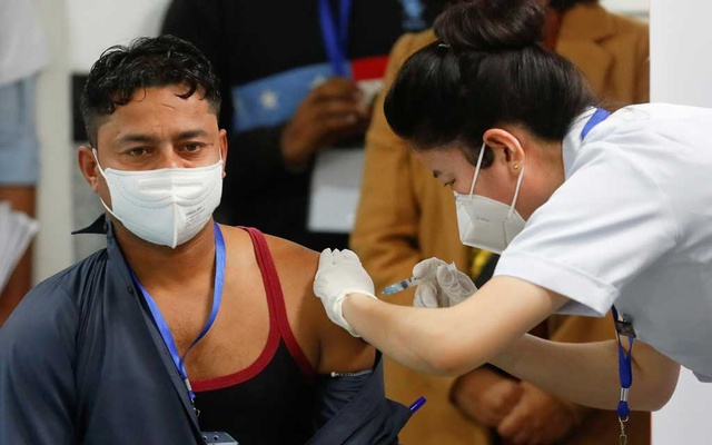 Sanitation worker Manish Kumar, who according to the officials is the first person in the country vaccinated against the COVID-19, receives a dose of Bharat Biotech's COVAXIN during the COVID-19 vaccination campaign at AIIMS hospital in New Delhi, India, January 16, 2021. Photo: Reuters