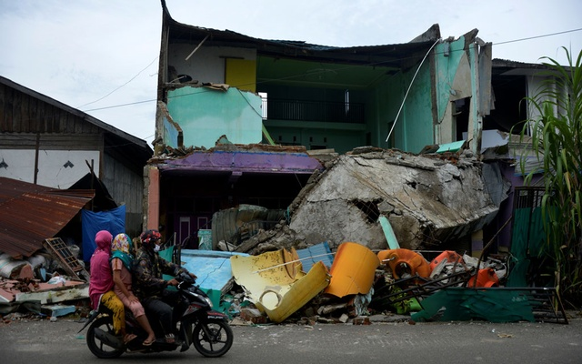 Locals ride a motorbike past a collapsed house following an earthquake in Mamuju, West Sulawesi province, Indonesia, January 17, 2021. Photo: Reuters