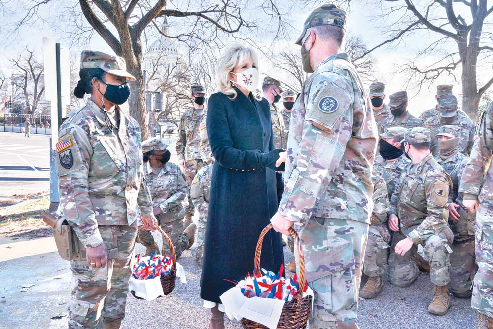 """Saying, """"The Biden's are a National Guard family,"""" first lady Jill Biden greets members of the National Guard with chocolate chip cookies outside the Capitol on January 22, in Washington, DC.photo : AFP"""
