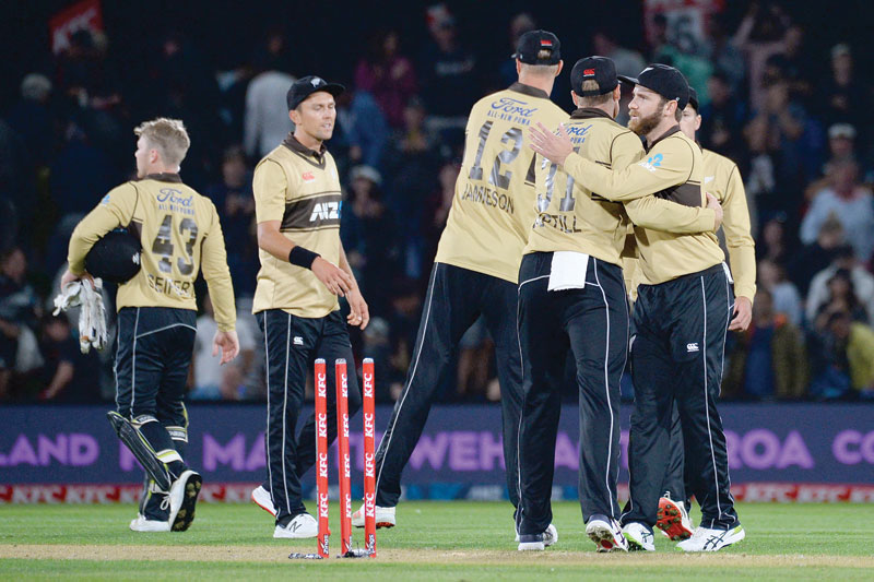 New Zealand's Kane Williamson (R) congratulates his teammates after winning the first Twenty20 cricket match between New Zealand and Australia at Hagley Park Oval in Christchurch on Monday.	photo: AFP