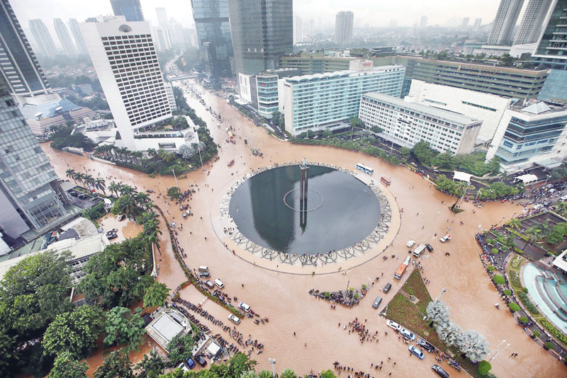 Motorists brave flooding at the Bank Indonesia traffic circle in Central Jakarta