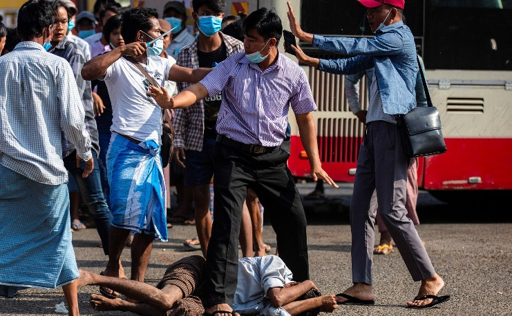 A military supporter points a sharp object as he confronts anti-coup protesters during a military support rally in Yangon on Thursday. (Reuters photo)