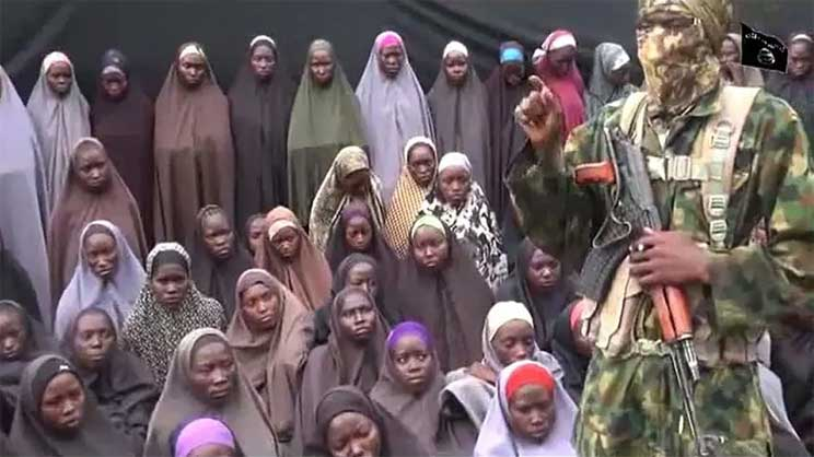 A video grab image from a YouTube clip posted in August 2016, purportedly by Islamist group Boko Haram, shows what is claimed to be one of the group's fighters alongside kidnapped Chibok girls HO AFP/File