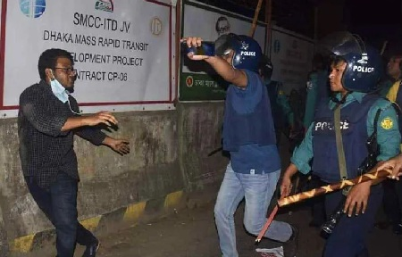 Police charging batons on an activist who brought out a procession in protest against death of writer Mushtaq Ahmed in jail.