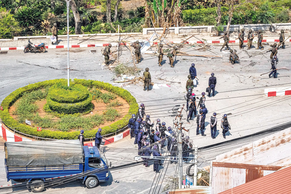 Soldiers and police clear a road blocked by protesters in Taunggyi, a city in Shan State, on February 28 as security forces continue to crackdown on demonstrations against the military coup.photo : AFP