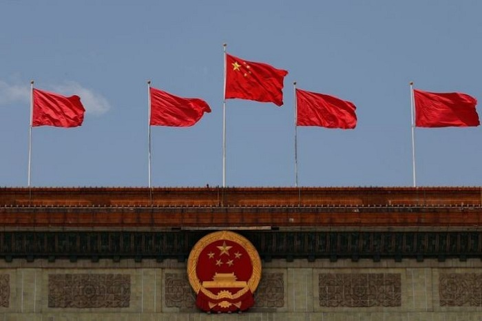 A Chinese flag flutters above the Chinese national emblem at the Great Hall of the People after the opening session of the National People's Congress (NPC) in Beijing, China May 22, 2020. File photo: Reuters